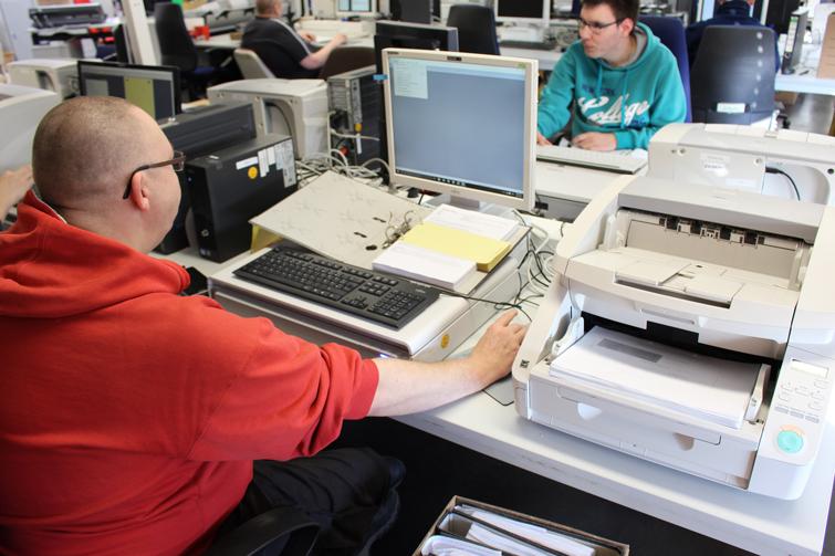 Ein Mitarbeiter digitalisiert Akten mit einem Scanner