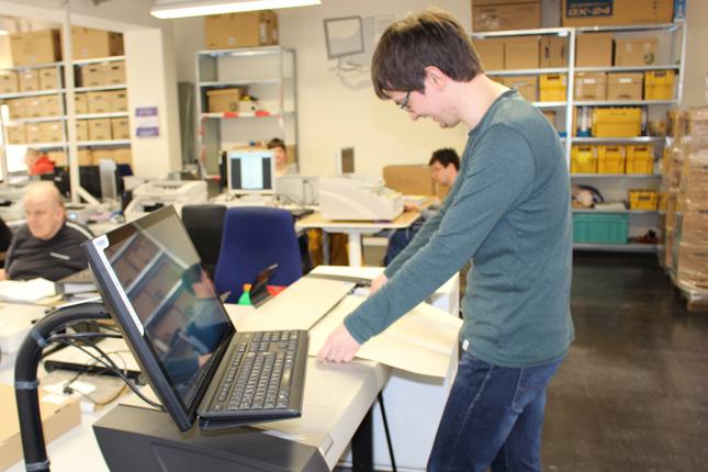 Ein Mitarbeiter digitalisiert eine große Zeichnung mit dem Großformatscanner