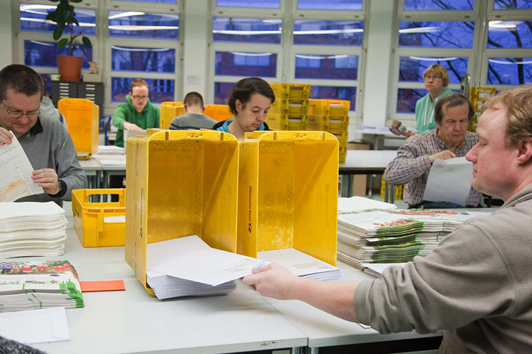 Eine Gruppe von Beschäftigten bearbeiten einen Auftrag zum Kuvertieren von Briefen