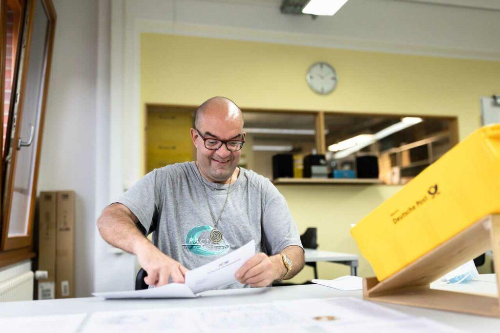 Ein Beschäftigter kuvertiert Briefe