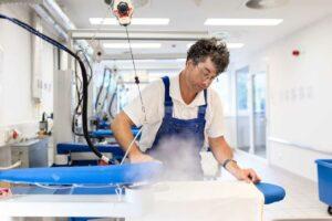 Ein Beschäftigter bearbeitet Bügelwäsche