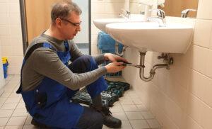 Hausmeister bei der Arbeit im Sanitärbereich