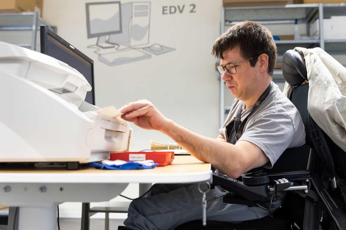 Ein Mitarbeiter digitalisiert Akten mit einem Einzugsscanner