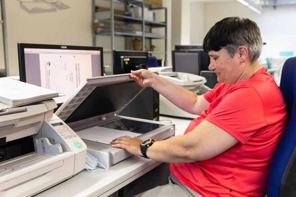 Eine Mitarbeiterin digitalisiert Unterlagen mit einem Flachbettscanner