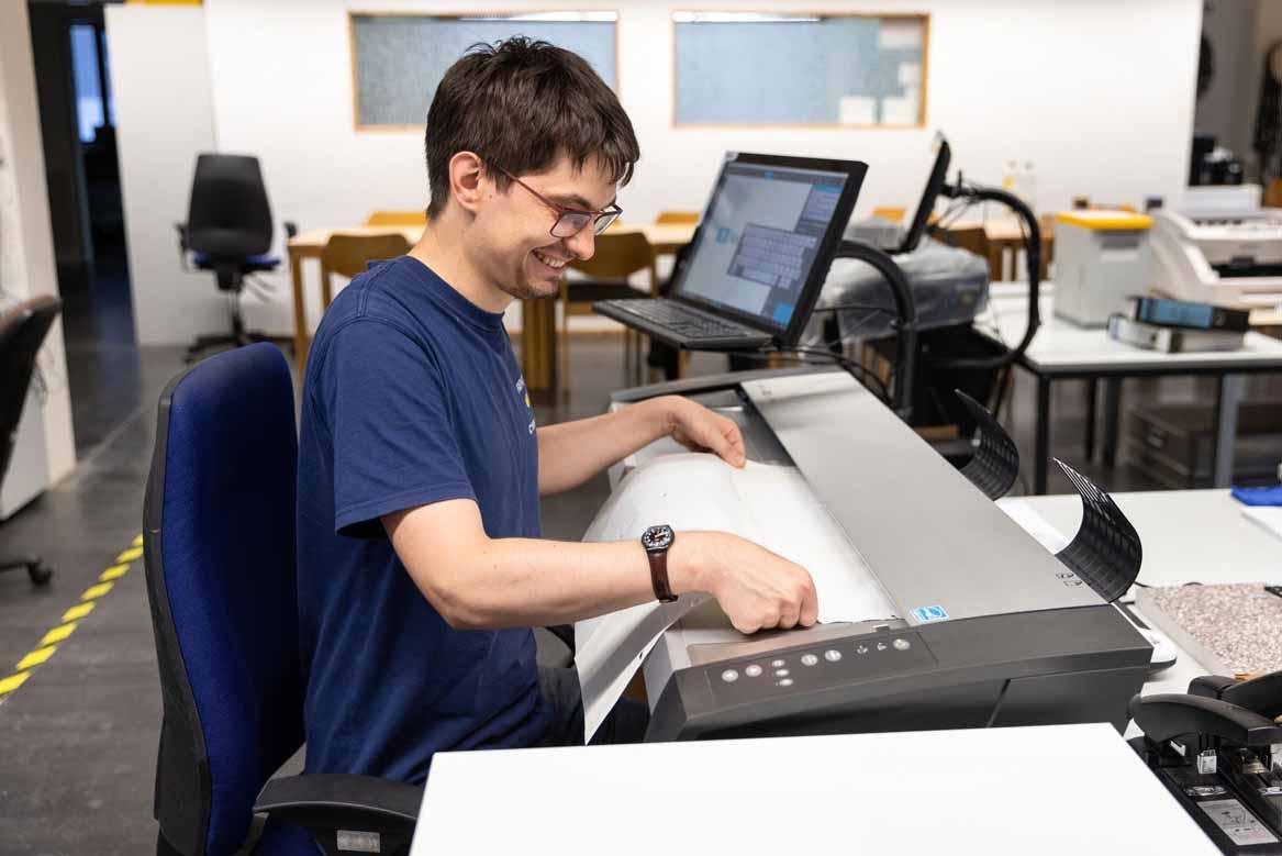 Ein Mitarbeiter digitalisiert einen Plan mit dem Großformatscanner