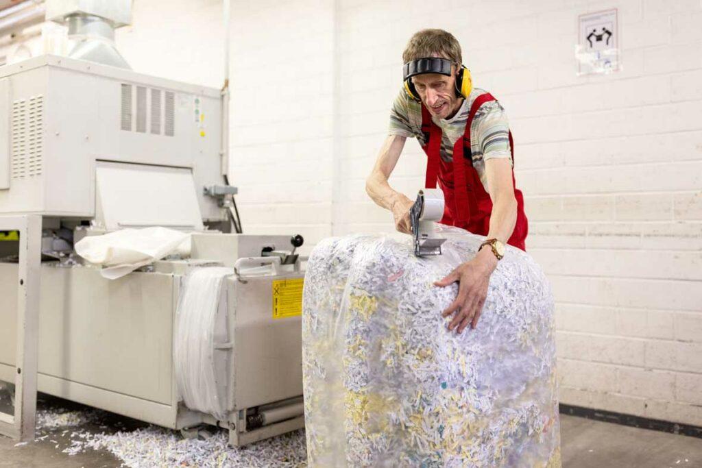 Ein Mitarbeiter verschließt einen Ballen mit Shreddergut