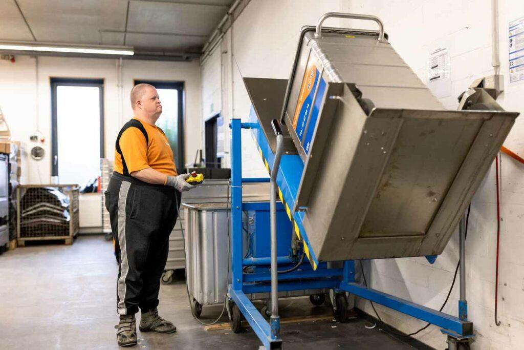 Ein Mitarbeiter bedient eine Kippvorrichtung für Aktencontainer