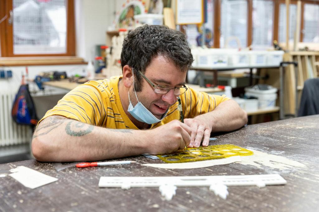 Ein Mitarbeiter zeichnet das Motiv auf das Holz