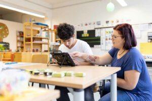 Eine Gruppenleiterin übt mit einem Beschäftigten am Spezialrechner