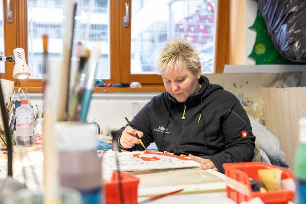Eine Mitarbeiterin bemalt die ausgesägten Objekte