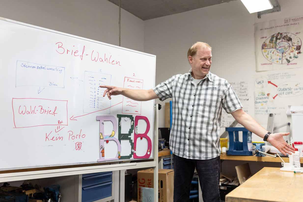 Ein Beschäftigter erklärt seinen Kollegen was er gelernt hat