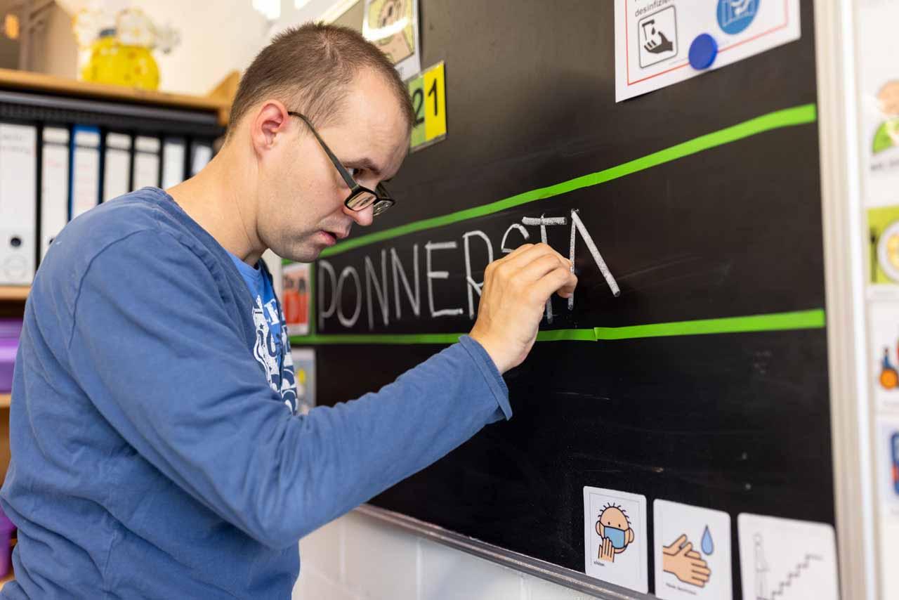 Ein Beschäftigter des BFB übt das Schreiben von Wochentagen