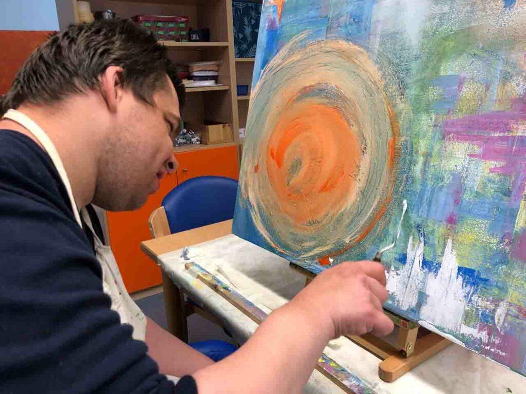 Ein Beschäftigter im BFB malt ein Bild