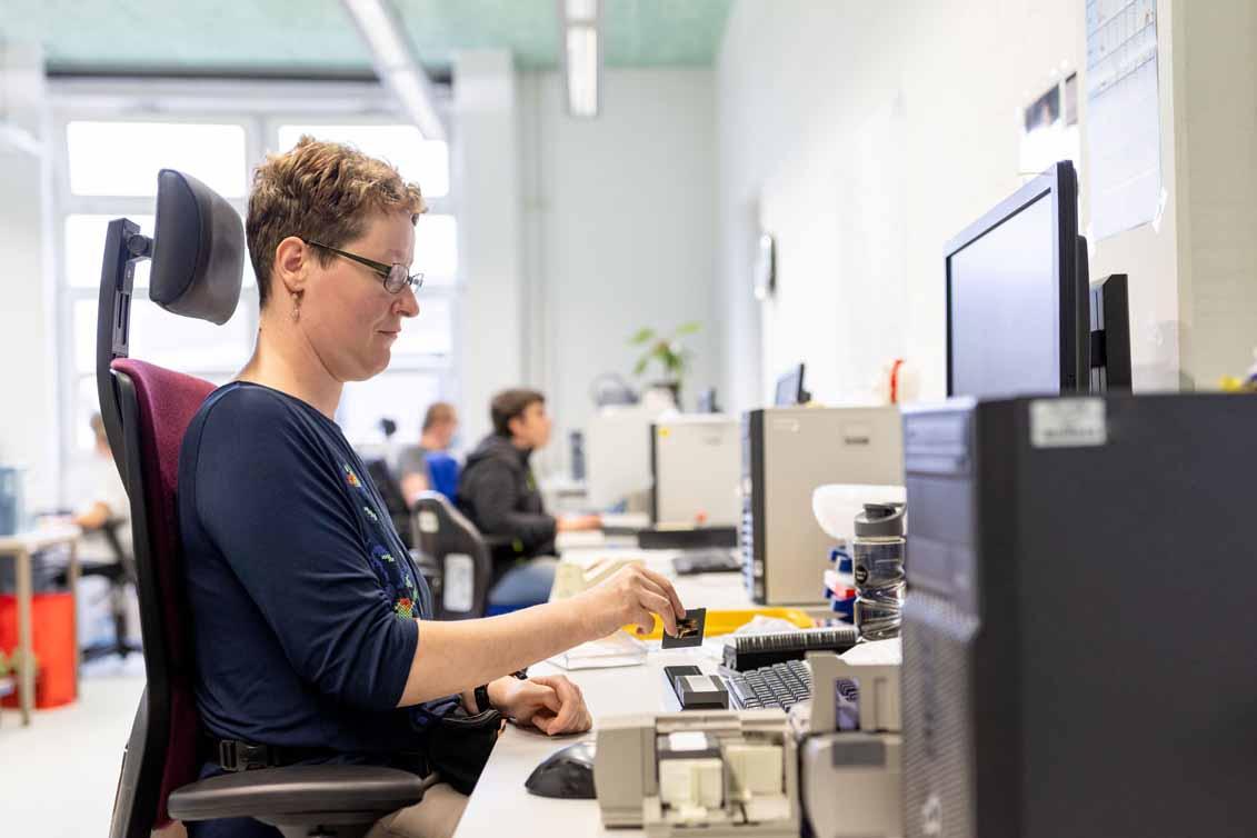 Eine Mitarbeiterin digitalisiert Dias