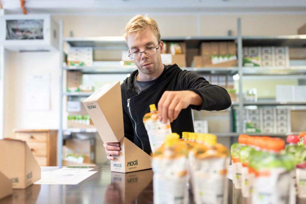 Ein Beschäftigter verpackt verschiedene Produkte im Rahmen des Fullfilment
