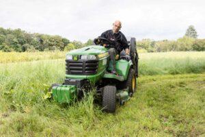 Ein Beschäftigter beim Rasen mähe mit einem Rasentraktor
