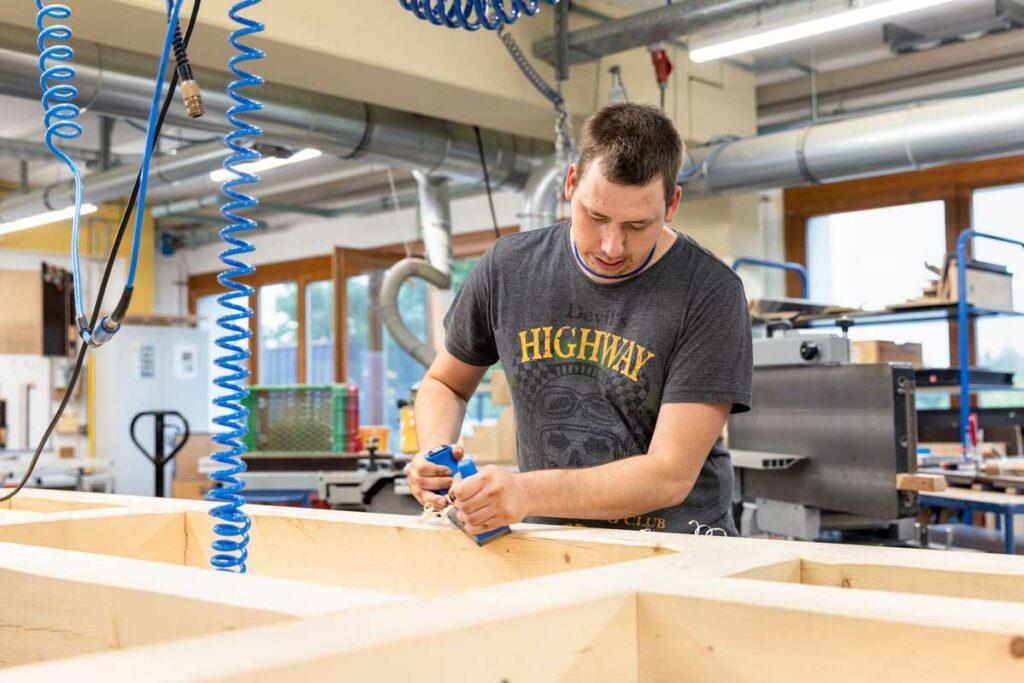 Ein Beschäftigter bearbeitet einen Holzrahmen mit einem Hobel