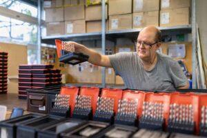 Ein Mitarbeiter der Lohnverpackung konfektioniert Bohrer in Aufbewahrungsboxen