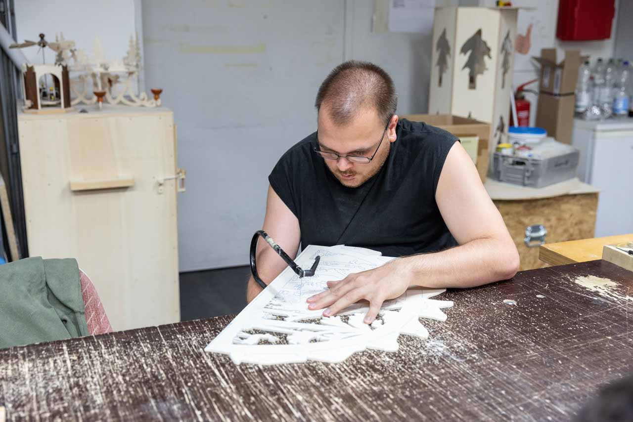 Ein Mitarbeiter sägt die vorgezeichneten Motive aus