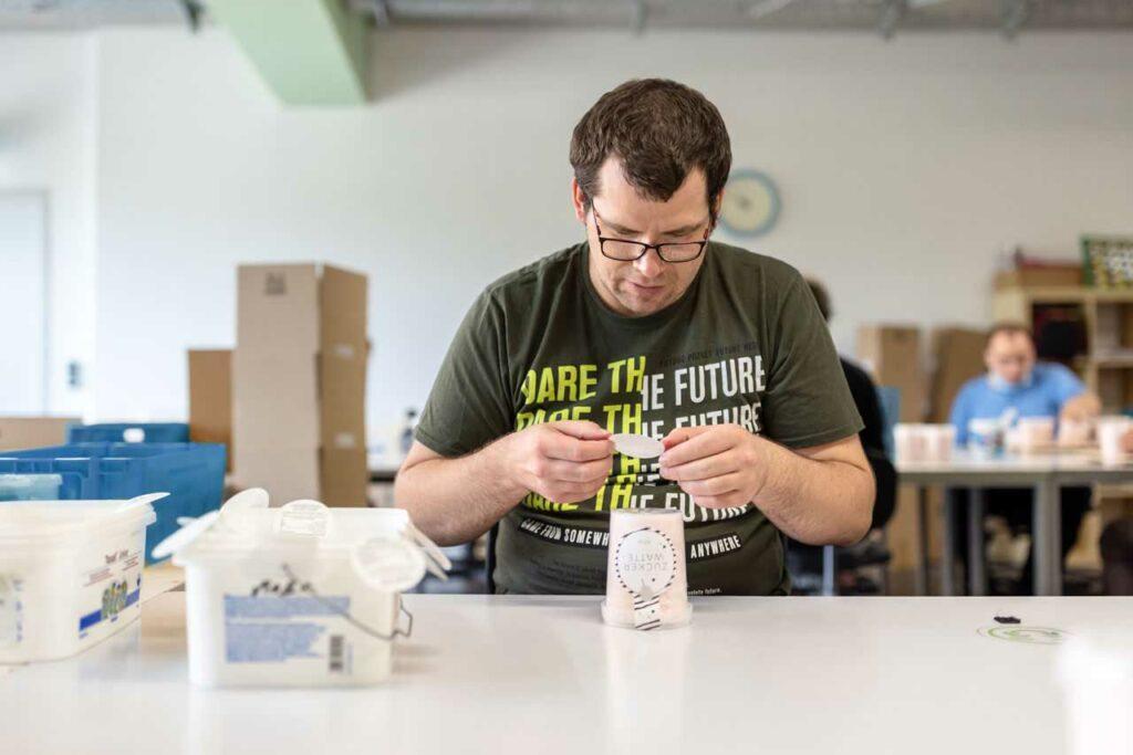 Ein Beschäftigter beklebt einen Becher mit Zuckerwatte