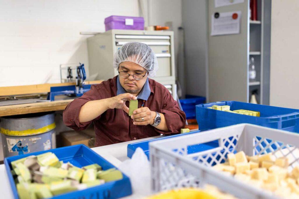 Ein Beschäftigter konfektioniert Seife in eine Faltschachtel
