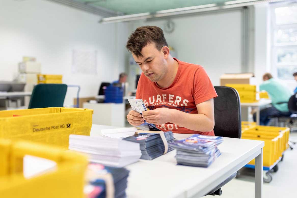 Ein Mitarbeiter kuvertiert Flyer manuell in Briefumschläge