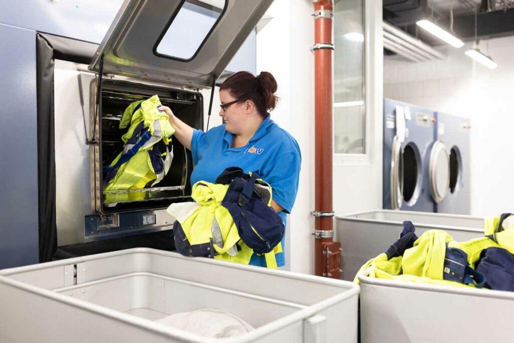 Eine Beschäftigte entleert eine Industriewaschmaschine